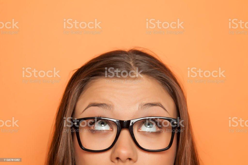 半肖像的一個年輕女孩與眼鏡抬頭看 - 免版稅一個人圖庫照片
