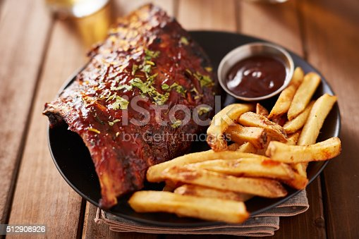 half rack barbecue rib platter with french fries on rustic wooden table