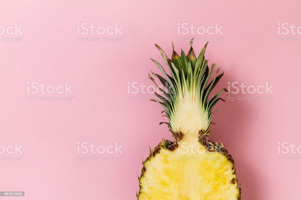 Half slice of beautiful fresh appetizing tasty pineapple on pink background. Top View. Horizontal. Copy Space. Conceptual. stock photo