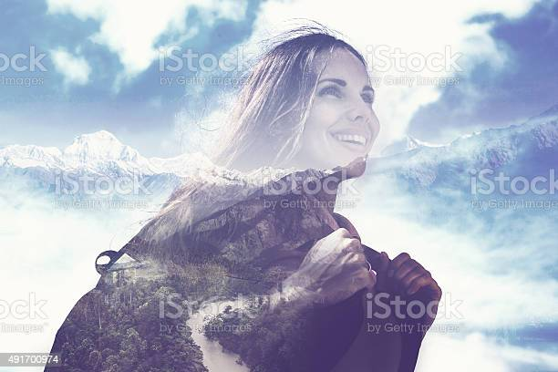 Photo of half transparent woman's portrait overlaying the mountain landscape