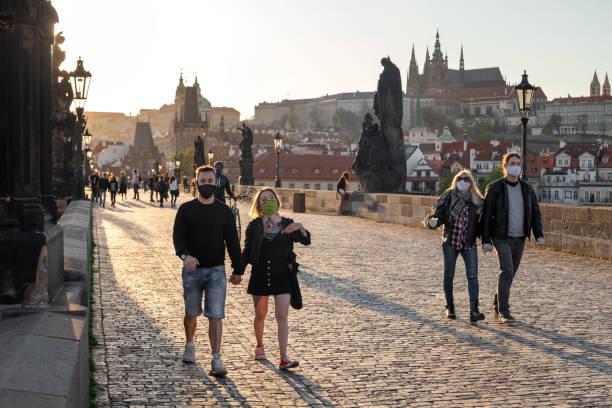 halvtomt karlsbron i prag under koronarviruspandemin, med människor som går i skyddande ansiktsmasker - walking home sunset street bildbanksfoton och bilder