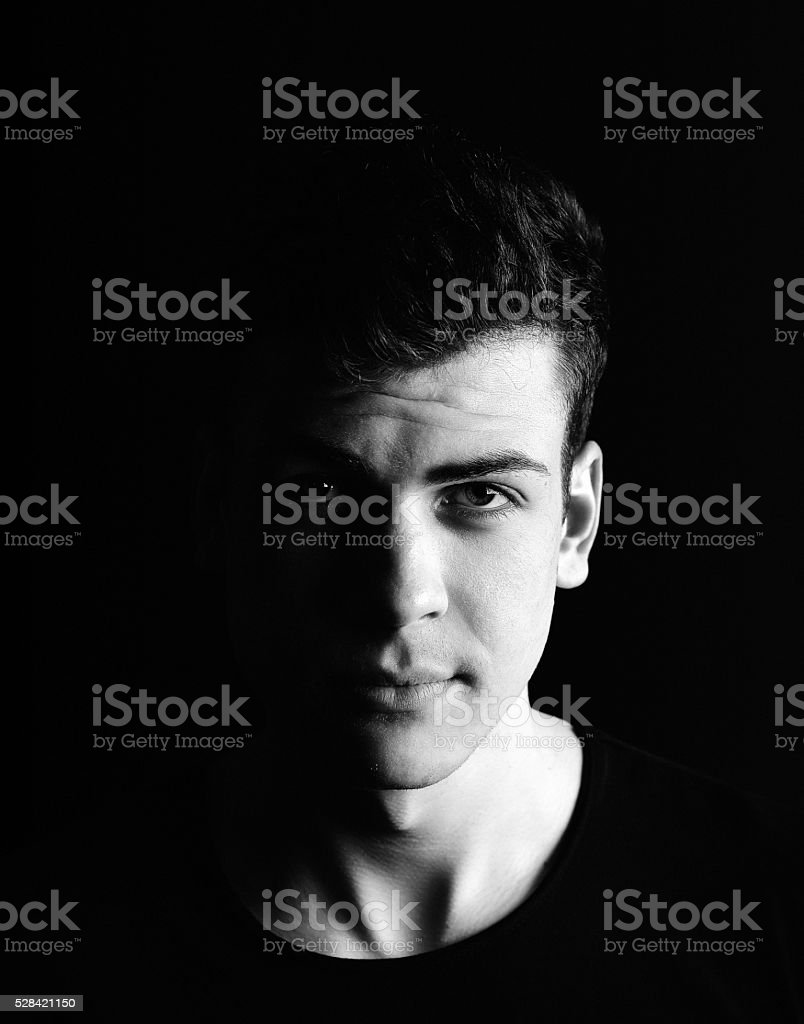 half-face young man portrait in low-key stock photo