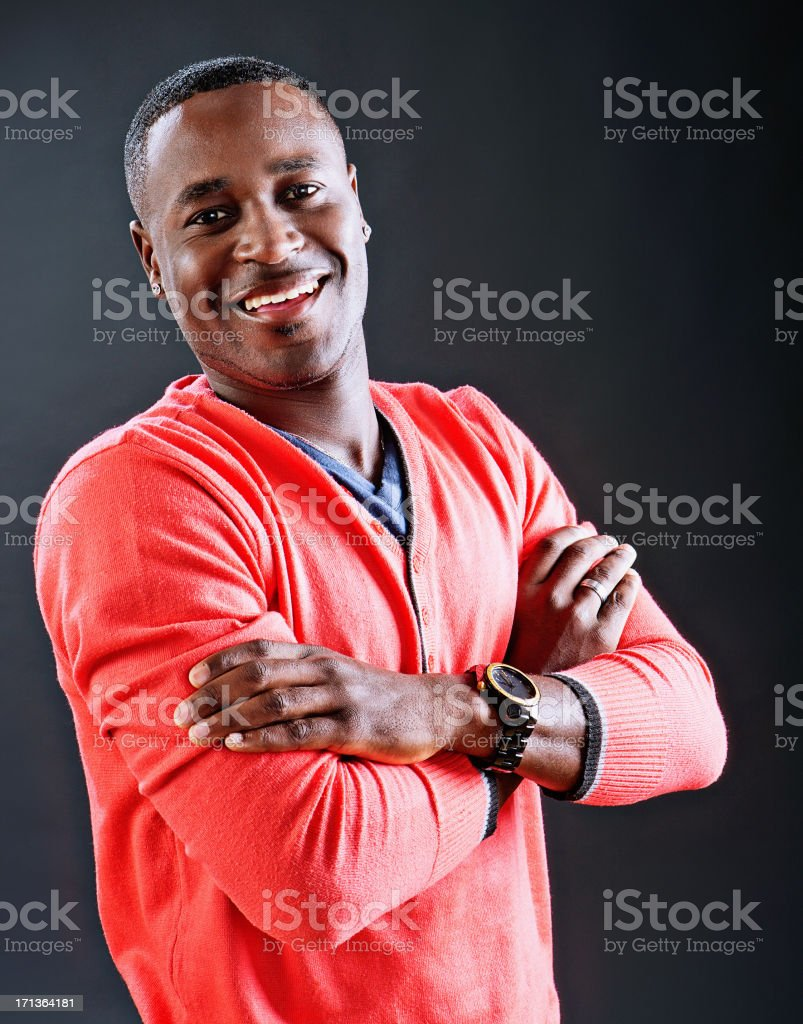 Half-length portrait of laughing man with folded arms against black stock photo