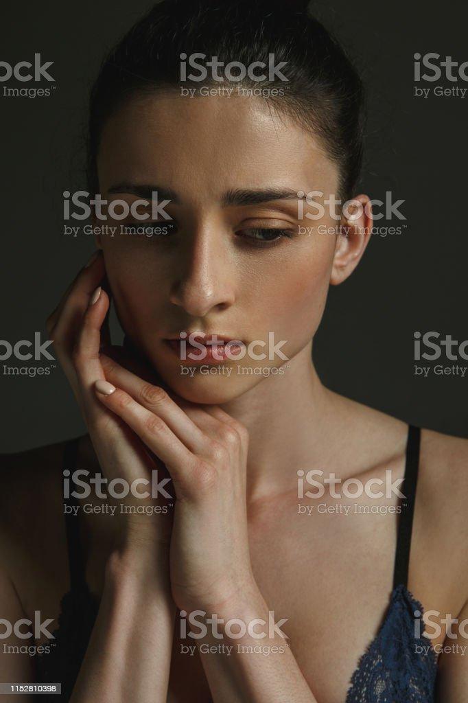 Half-length portrait of young sad woman in underwear on dark studio...