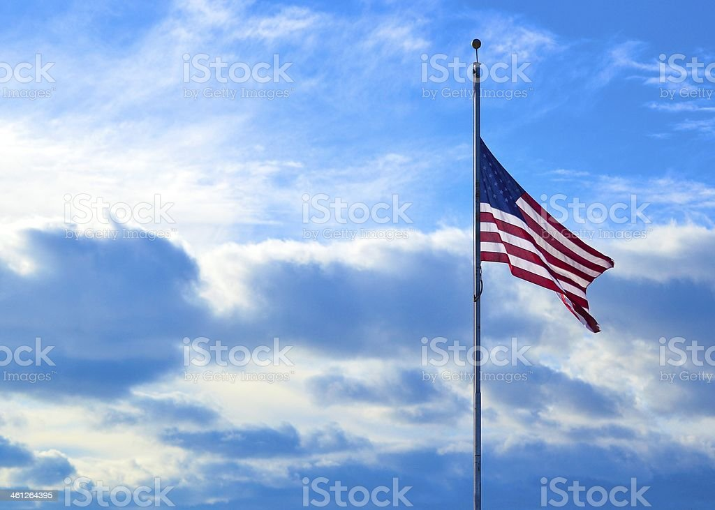Half-Mast American Flag Against Blue Sky stock photo