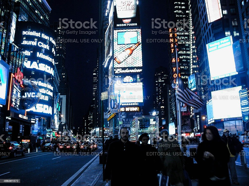 Half-mast American Flag amid Illuminated Billboards and Pedestrians