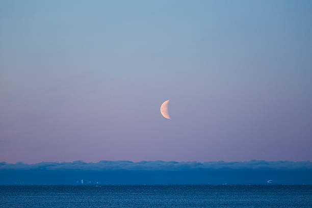 Half-moon over arctic ocean with clouds and floe stock photo