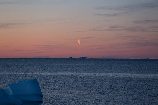 Half-moon over Icebergs floating near horizon stock photo