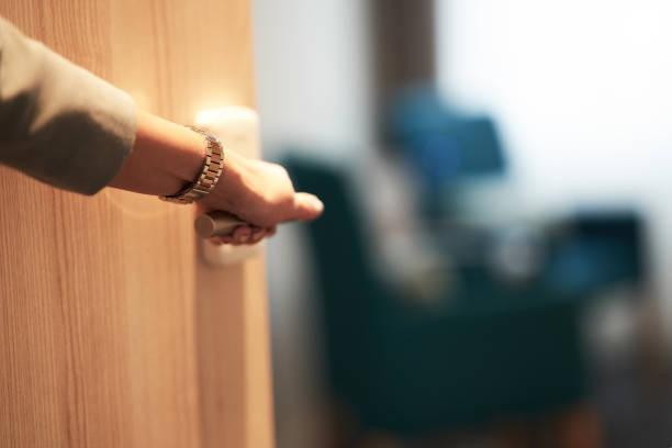 Halboffene Tür eines Hotelzimmers mit Hand – Foto