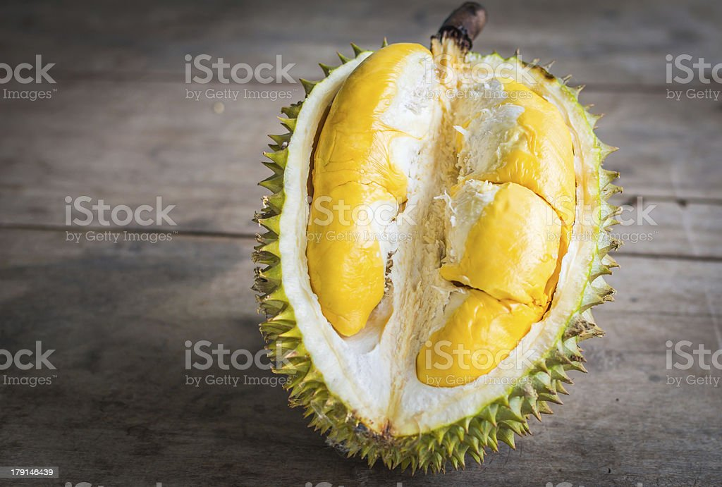 A half-peeled Durian fruit on a wooden floor stock photo