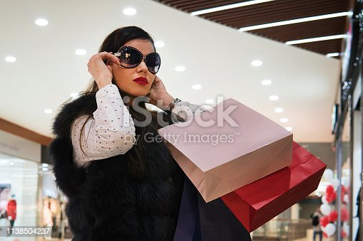 istock Half-shot of young attractive girl putting on sun glasses after shopping in shopping centre. Trendy brunette girl with paper bags walking in luxury store. Spending money in shops. Hunting for brands. 1138504237