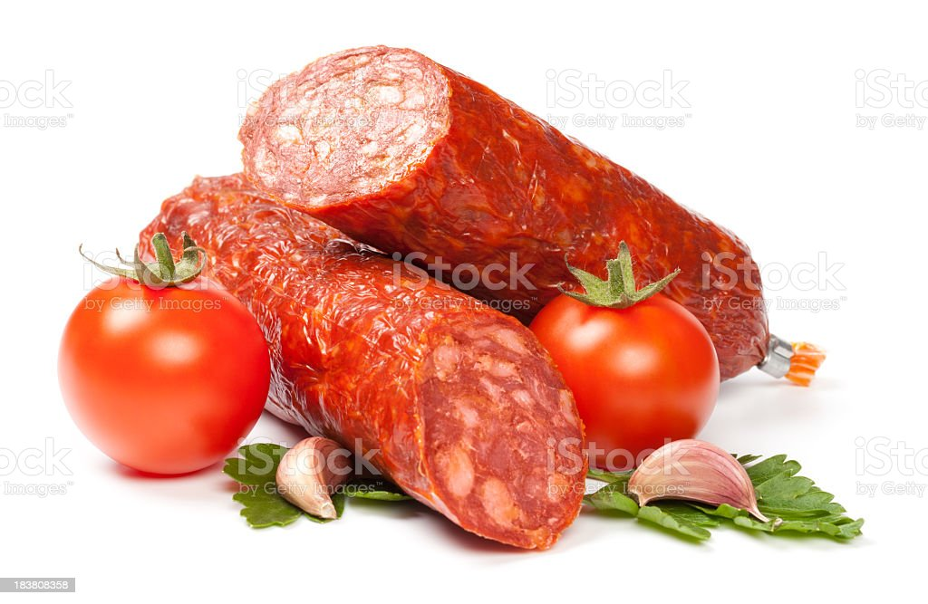 Half-sliced sausage roll, and tomatoes on white background  stock photo