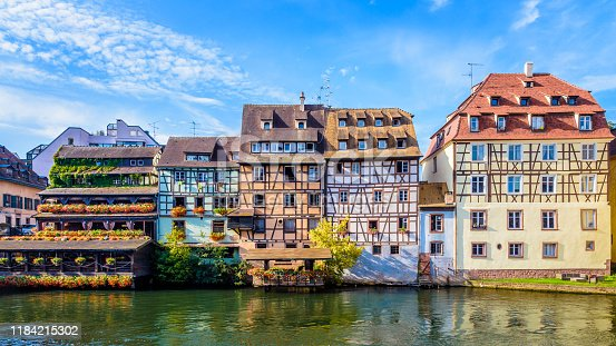 Panoramic front view of typical half-timbered buildings with pastel facades lining the river Ill in the Petite France quarter in Strasbourg, France, on a sunny morning.
