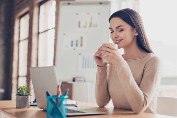 half-turned portrait of cute calm peaceful feeling comfort coziness pretty tender gentle expert qualified travel agent having rest holding tasty fresh cup of tea in hands sitting at the desktop - fare una pausa foto e immagini stock