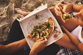 Shot of a young unrecognizable couple having a small picnic date and sharing a pizza on the beach at sunset