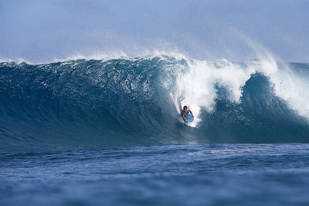Halfway down the face of a big barreling wave stock photo