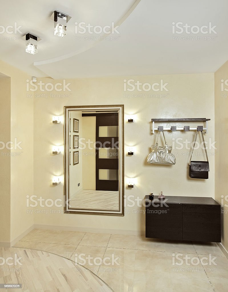 Hall in beige tones with hallstand and golden mirror stock photo