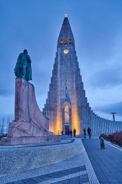 """Hallgrímskirkja in Reykjavik Reykjavik, Iceland - February 16, 2020: tourists visiting the square outside Hallgrímskirkja """"u2013 the Church of Hallgrímur, a Evangelic-Lutheran Church. In foreground the statue of Leifur Eiríksson. Reykjavik. Iceland. Hallgrímskirkja church stock pictures, royalty-free photos & images"""