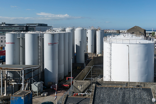 A number of storage tanks at the harbour seen during a sunny afternoon. two different shapes and sizes can be seen in the area near the harbour entrance.