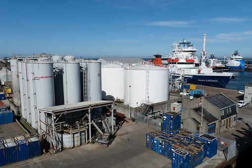 A number of storage tanks at the harbour seen during a sunny afternoon. two different shapes and sizes can be seen in the area near the harbour entrance. Oil support vessels can also be seen alongside this industrial complex which supports the oil industry.