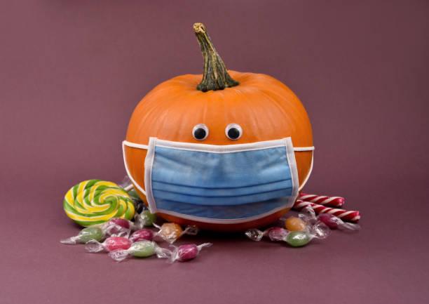 calabaza hallowee con máscara protectora y caramelos imágenes de stock - halloween covid fotografías e imágenes de stock
