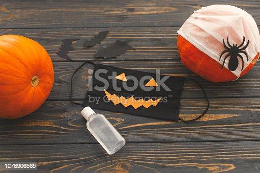 Halloween 2020. Halloween creative scary face mask, pumpkin, disinfection gel bottle, bat and spider decoration on dark wood. Celebrating halloween in safe way due to coronavirus pandemic