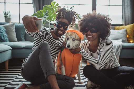 Young couple celebrating Halloween. They wear costumes, smiling, taking selfie and enjoy in holiday. Dog is with them and wear costume