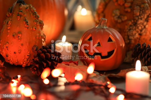 Halloween, autumn scene with pumpkins.  Group of objects includes: candles, pumpkins, jack o' lanterns, fall leaves, and pine cones.