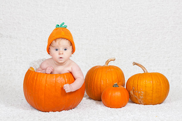 Halloween baby inside pumpkin in pumpkin hat stock photo