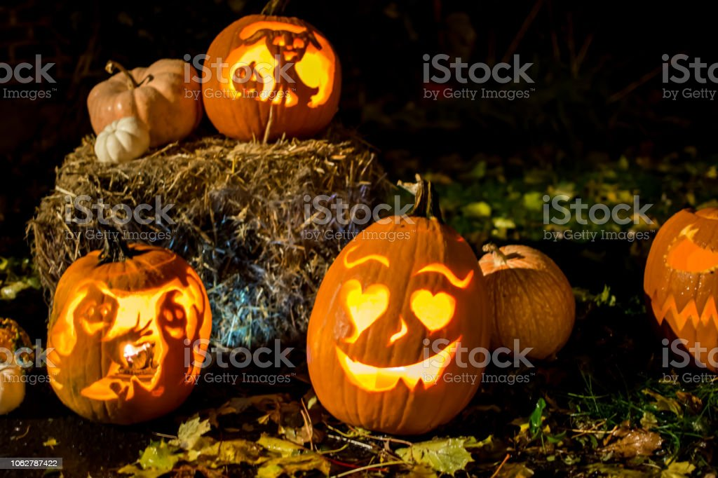 Halloween background cute glowing Jack o'lantern  pumpkins on hay stacks at night stock photo