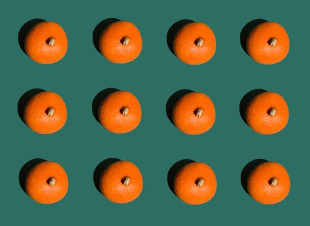 halloween hintergrund geometrischen reihen von leuchtend orange kürbisse auf dunkelgrün. nahtlose muster. pop art-stil. kreative konzeptbild. thanksgiving - hokkaido kürbis zubereiten stock-fotos und bilder