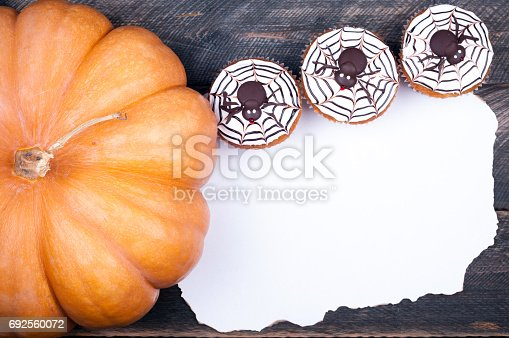 istock Halloween background. Old paper, pumpkin muffin with spiders for halloween party on old rustic wooden table. Copy space 692560072