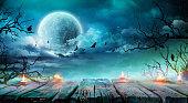 ハロウィン背景 - キャンドルと満月と不気味な夜の枝古いテーブル