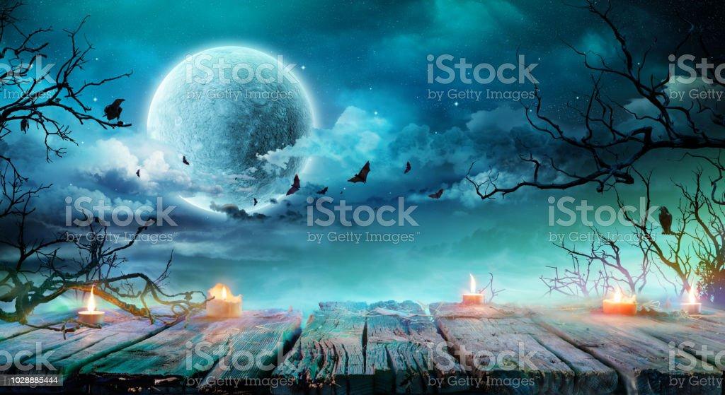 Halloween-Hintergrund - alten Tisch mit Kerzen und Niederlassungen in der gruseligen Nacht mit Vollmond – Foto
