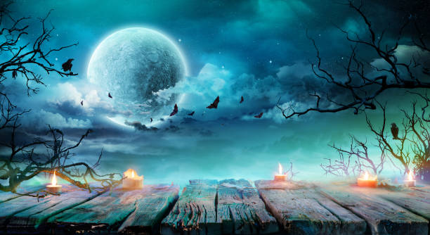 halloween background  - old table with candles and branches at spooky night with full moon - horror stock pictures, royalty-free photos & images
