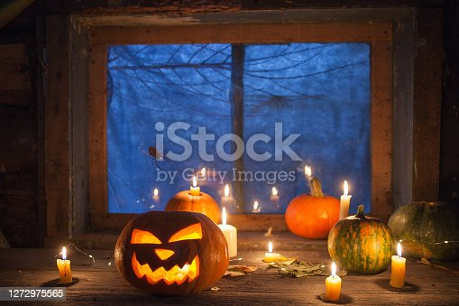 Halloween background, pumpkins and Jack-o ' - lantern next to burning candles on the background of an ominous night window with a spider