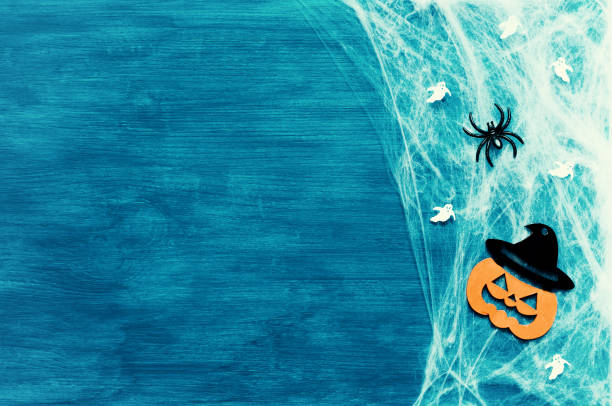 halloween background. spider web, spiders and smiling jack decorations as symbols of halloween on the green background - halloween stock photos and pictures