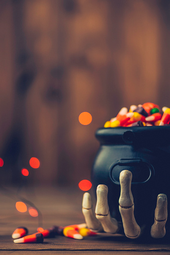 Halloween background with cauldron, candy and skeleton hand