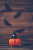 istock Halloween background with cute pumpkin witch and bats 1173604226
