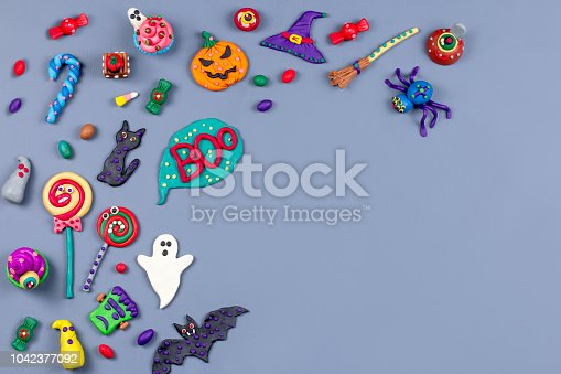 1057069236 istock photo Halloween background with decorations. Black cat, bats, witches hat and broomstick with orange pumpkins. Top view 1042377092