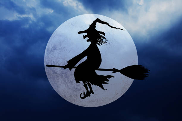 Halloween background with full moon and flying witch Halloween witch. Silhouette of smiling wicked witch flying on broomstick with hat with a wart on the nose on dark spooky night cloudy sky background. broom stock pictures, royalty-free photos & images