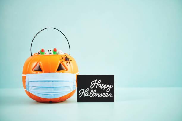 fondo de halloween con jack o'lantern lleno de caramelos usando una máscara facial - halloween covid fotografías e imágenes de stock