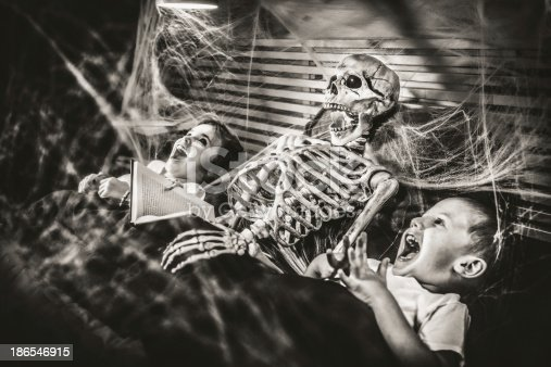 Little girl reading terror stories to her brother and a skeleton.