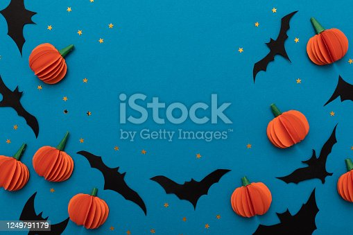 Halloween blue background with black bats and orange pumpkins. Modern design. Holiday party decoration. Flat lay.
