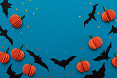 istock Halloween blue background with black bats and orange pumpkins. Modern design. Holiday party decoration. Flat lay. 1249791179