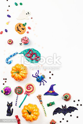 1057069236 istock photo Halloween border with decorations. Black cat, bats, witches hat and broomstick with orange pumpkins. Top view 1042377076