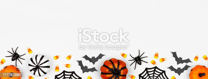 1057069236 istock photo Halloween bottom border banner flat lay of pumpkins, candy and decor, over a white background 1172823957
