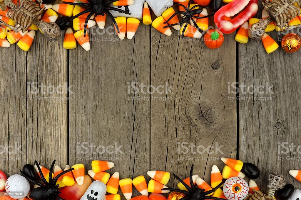 Halloween candy and decor double border over rustic wood stock photo