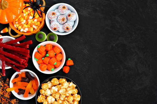 halloween candy buffet table side border over a black background with copy space - halloween candy стоковые фото и изображения