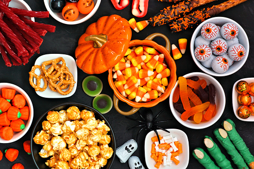 Halloween candy buffet table scene over a black stone background. Assortment of sweet, spooky treats. Above view.